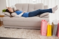 Woman lying on couch with shopping bags at home in the living room