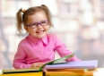 Happy child girl in eyeglasses reading books sitting at table