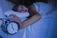 Awakening woman stopping her alarm clock at night in the bedroom