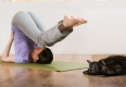 Woman in a traditional stretching yoga pose at home with her cat