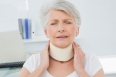 Close-up of a senior woman wearing cervical collar with eyes closed in the medical office