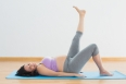 Pregnant woman lying on mat lifting her leg in a fitness studio