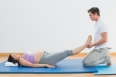 Masseur lifting pregnant womans legs on blue mat in a fitness studio