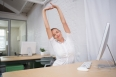 Young businesswoman stretching hands in office
