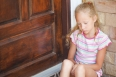 sad little girl sitting near a door on the background of an bric