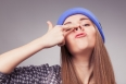 Young woman holding up fingers on nose and making silly expression